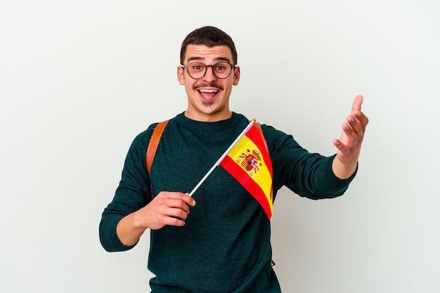 Junger mann, der englisch isoliert auf weißer wand studiert und eine angenehme überraschung empfängt, aufgeregt und hände hebend