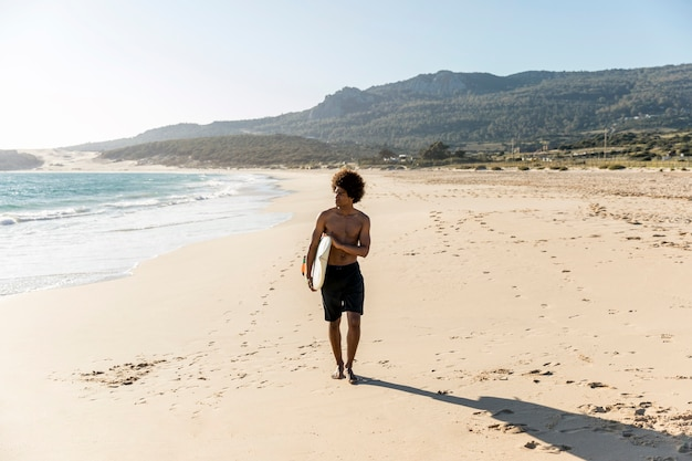 Junger mann, der entlang tragendes surfbrett der küste geht