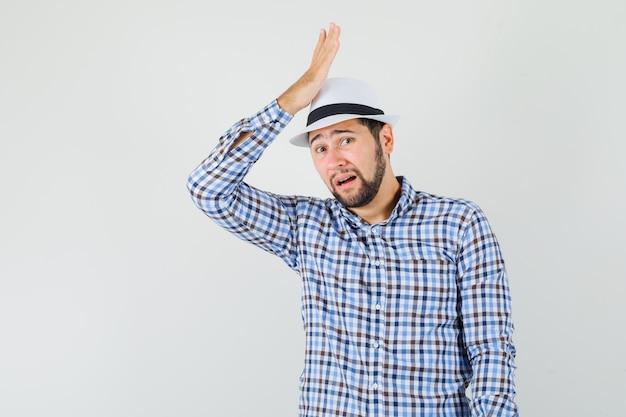Junger mann, der erhabene handfläche über kopf in kariertem hemd, hut hält und entschuldigung, vorderansicht schaut.
