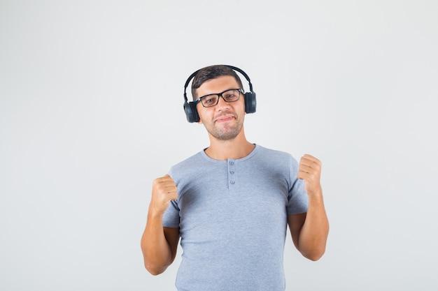 Junger mann, der erhobene fäuste in grauem t-shirt, brille, kopfhörern macht und glücklich schaut