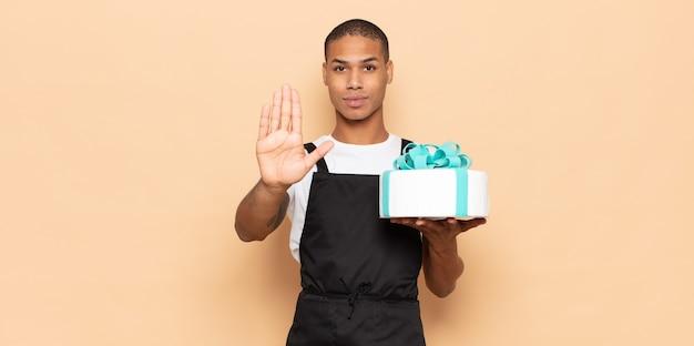 Junger mann, der ernst, streng, unzufrieden und wütend aussieht und offene handfläche zeigt, die stoppgeste macht