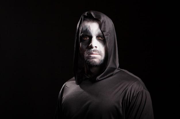 Junger mann, der ernsthaft in die kamera schaut, verkleidet wie sensenmann. halloweenkostüm.