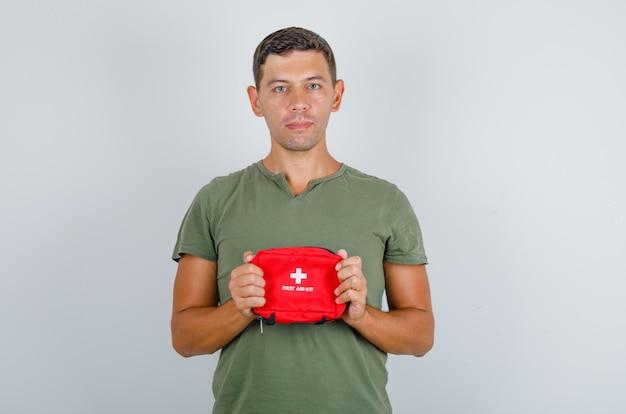 Junger mann, der erste-hilfe-kit im armeegrünen t-shirt hält und vorsichtig schaut, vorderansicht.