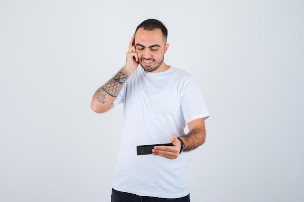 Junger mann, der etwas am telefon anschaut und die hand in weißem t-shirt und schwarzer hose auf das ohr drückt und glücklich aussieht