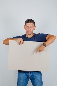 Junger mann, der etwas auf plakat im blauen t-shirt, in den jeans und in der positiven vorderansicht zeigt.