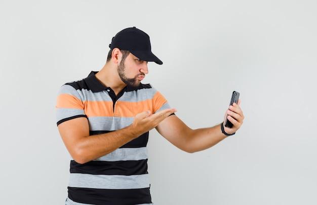 Junger mann, der etwas auf video-chat im t-shirt, in der mütze und im verwirrten blick bespricht. vorderansicht.