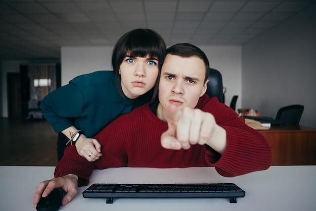 Junger mann, der etwas geschäftsfrau auf dem computerbildschirm zeigt. überrascht in die kamera schauen