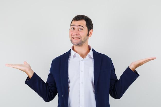 Junger mann, der etwas im hemd präsentiert oder vergleicht