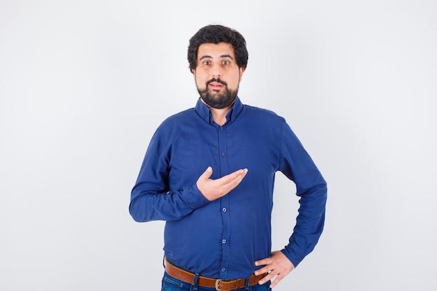 Junger mann, der etwas im königsblauen hemd beiseite zeigt und beunruhigt aussieht. vorderansicht.