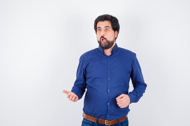 Junger mann, der etwas im königsblauen hemd bespricht und unzufrieden aussieht. vorderansicht.