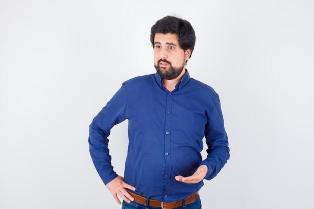 Junger mann, der etwas im königsblauen hemd erklärt und gesprächig aussieht, vorderansicht.