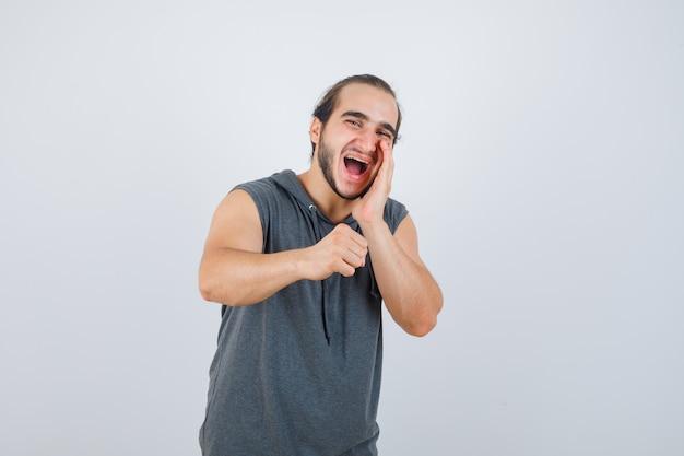 Junger mann, der etwas schreit, während er geballte faust im ärmellosen kapuzenpulli erhebt und glücklich aussieht, vorderansicht.