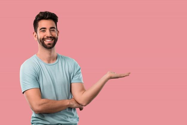 Junger mann, der etwas über einem rosa hintergrund hält