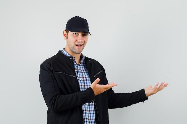 Junger mann, der etwas zeigt oder im hemd, in der jacke, in der mütze begrüßt und sanft schaut, vorderansicht.