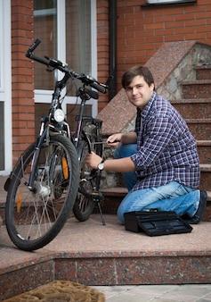 Junger mann, der fahrrad auf der veranda seines hauses repariert