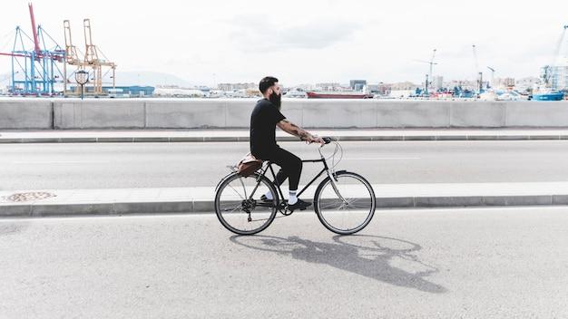 Junger mann, der fahrrad auf straße nahe dem hafen fährt