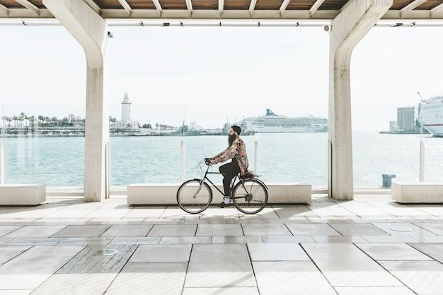 Junger mann, der fahrrad nahe dem hafen fährt