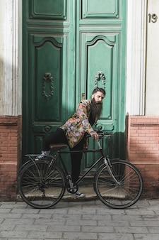 Junger mann, der fahrrad vor großer geschlossener tür fährt