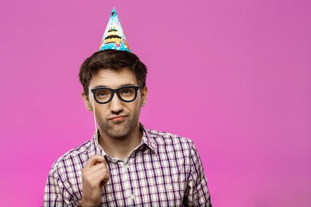 Junger mann, der falsche brille über lila wand trägt. geburtstagsfeier.