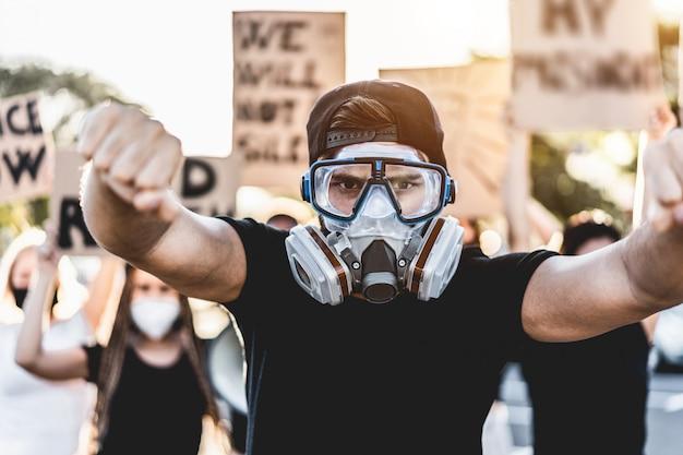 Junger mann, der faustsymbol für allgemeinen protest auf der straße tut