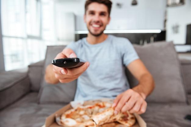 Junger mann, der fernbedienung hält und den knopf drückt, während er pizza isst.