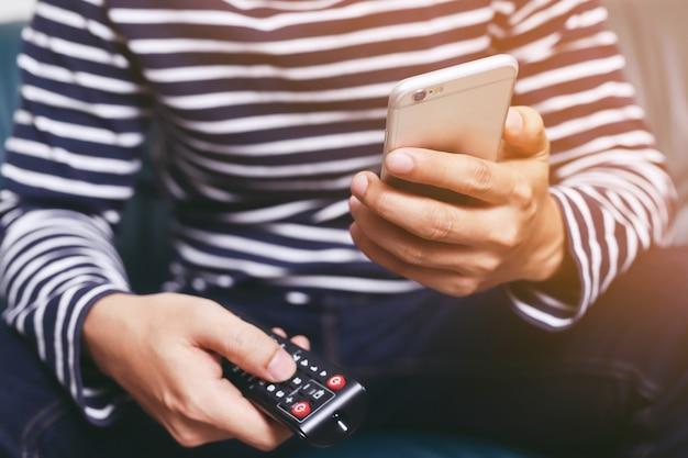 Junger mann, der fernsehfernbedienung und mobiles smartphone benutzt, sitzt auf einem sofa.