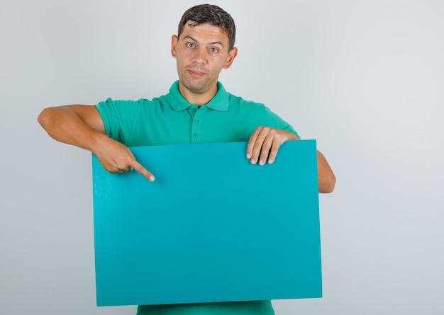 Junger mann, der finger auf blaues plakat im grünen t-shirt, vorderansicht zeigt.