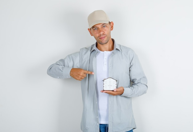 Junger mann, der finger auf hausmodell im t-shirt mit kappe zeigt
