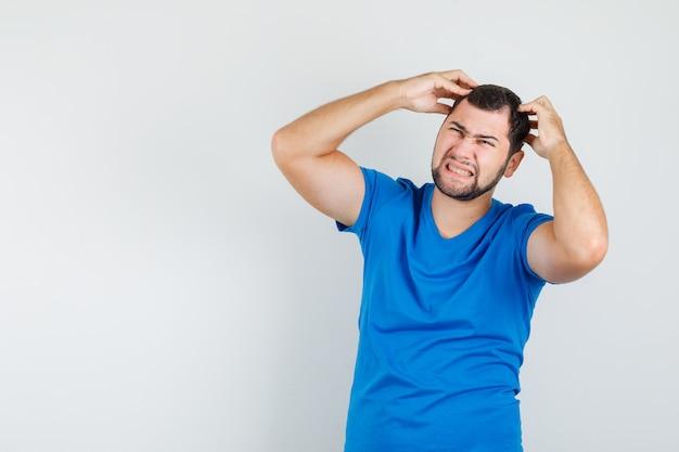 Junger mann, der finger auf kopf im blauen t-shirt hält und gereizt aussieht