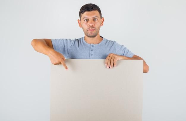 Junger mann, der finger auf leeres plakat im grauen t-shirt zeigt