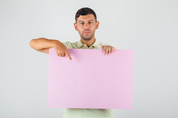 Junger mann, der finger auf leeres plakat im t-shirt zeigt