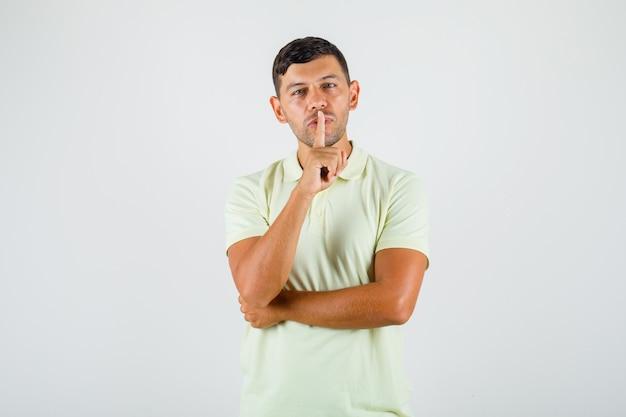 Junger mann, der finger auf lippen in t-shirt setzt und defensiv schaut