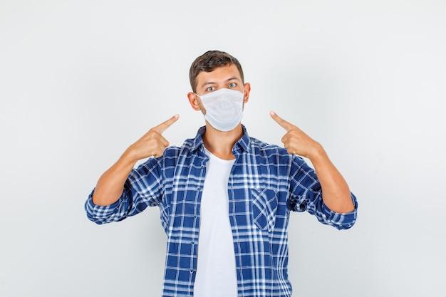 Junger mann, der finger auf medizinische maske im hemd zeigt und vorsichtig, vorderansicht schaut.