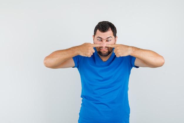 Junger mann, der finger auf nase in blauem t-shirt drückt und seltsam aussieht