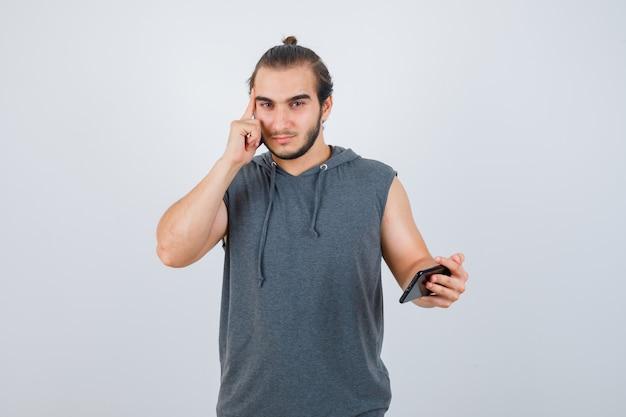 Junger mann, der finger auf schläfen im kapuzen-t-shirt hält und nachdenklich, vorderansicht schaut.