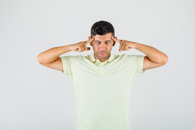 Junger mann, der finger auf seine schläfen im t-shirt legt und klug aussieht
