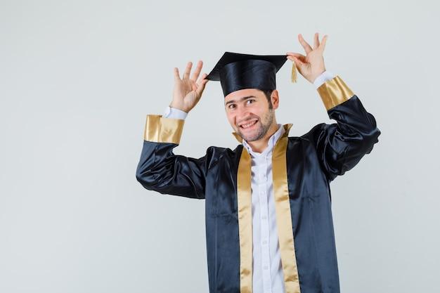 Junger mann, der finger auf seiner kappe in der abschlussuniform hält und fröhlich, vorderansicht schaut.