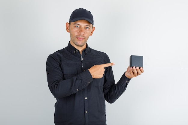 Junger mann, der finger auf uhrbox im schwarzen hemd mit kappe zeigt