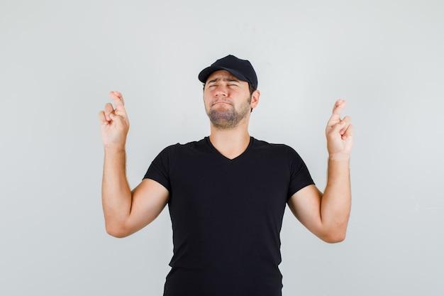 Junger mann, der finger im schwarzen t-shirt gekreuzt hält
