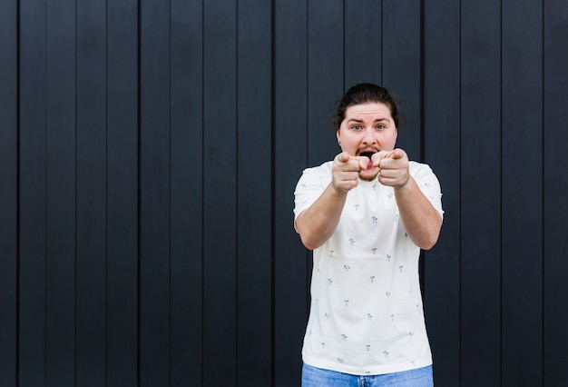 Junger mann, der finger in richtung zur kamera gegen schwarzen hintergrund schreit und zeigt