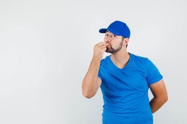 Junger mann, der finger küsst, während köstliche geste im blauen t-shirt und in der mütze macht und freudig aussieht