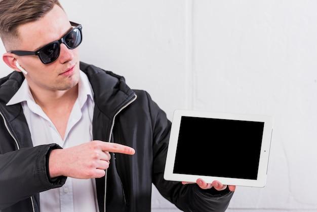 Junger mann, der finger über der digitalen tabelle steht gegen weiße wand zeigt
