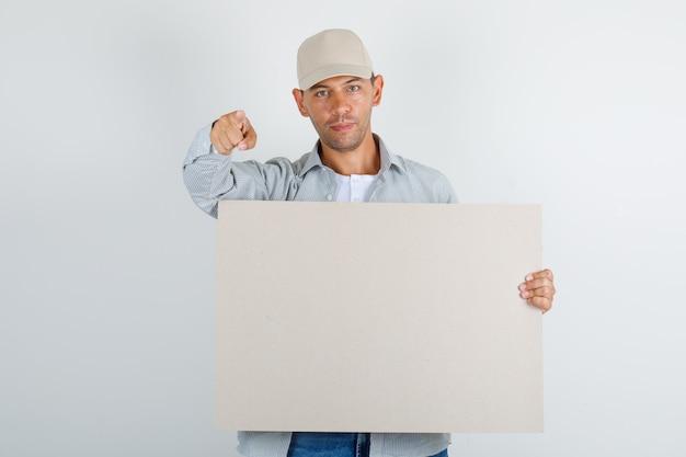 Junger mann, der finger zur kamera mit plakat im hemd mit kappe, jeans zeigt