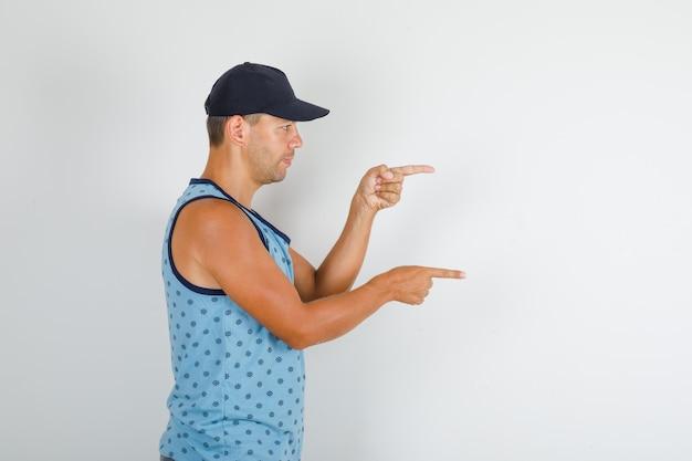 Junger mann, der finger zur seite im blauen unterhemd mit kappe zeigt