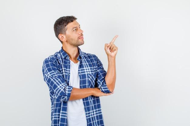 Junger mann, der finger zur seite im hemd zeigt und konzentriert schaut. vorderansicht.