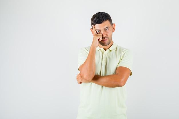 Junger mann, der fingerstütze auf stirn in t-shirt setzt und vorsichtig schaut.