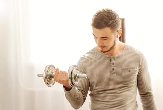 Junger mann, der fitnessübung zu hause tut
