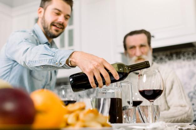 Junger mann, der flasche rotwein hält und in gläser, festlichen tisch, traditionelles und feierendes konzept gießt. großvater sitzt am tisch im hintergrund