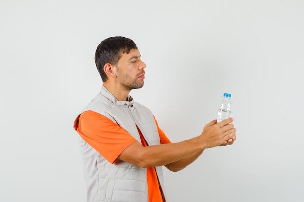 Junger mann, der flasche wasser in t-shirt, jacke, vorderansicht betrachtet.