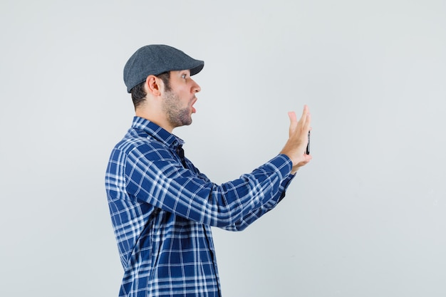Junger mann, der foto auf handy in hemd, mütze nimmt und erstaunt schaut.